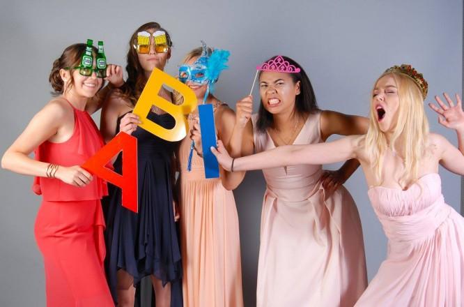 Gruppenfoto der besten Schulfreundinnen auf dem Abiball, mit Spaß-Accessoires