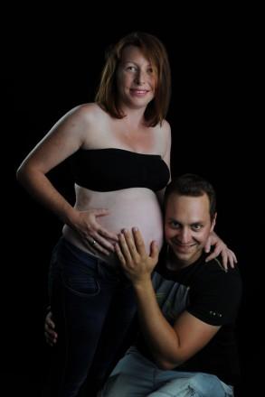 Zwei, die sich freuen: Werdender Vater horcht am Babybauch der werdenden Mutter