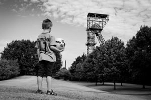 Foto Wolff-Foto des Monats Mai 2019: Junge in Fußballkleidung vor Förderturm, von Marco Adolphs